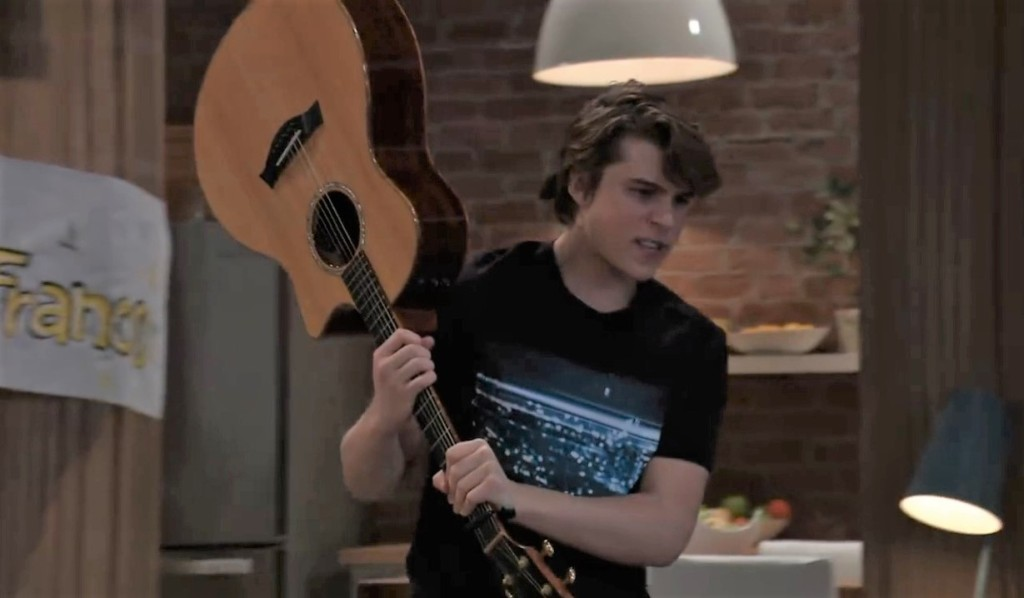 Cam answers the door with his guitar General Hospital