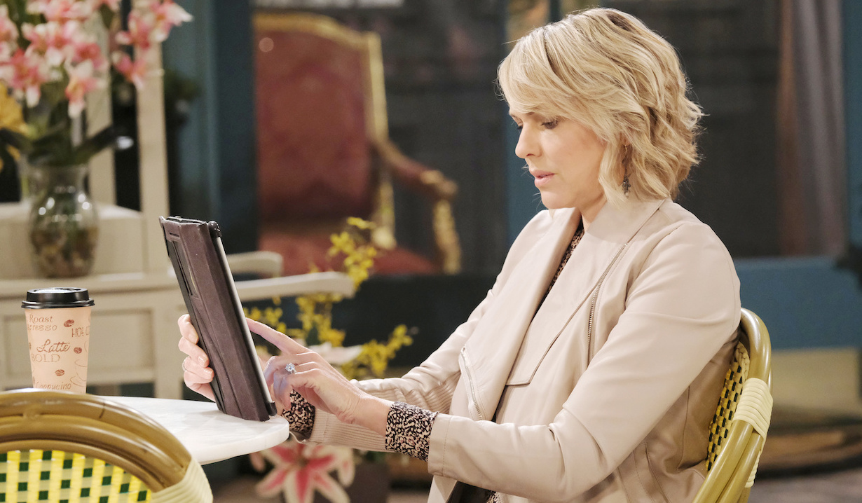 Nicole reads on her tablet in the Square on Days of Our Lives