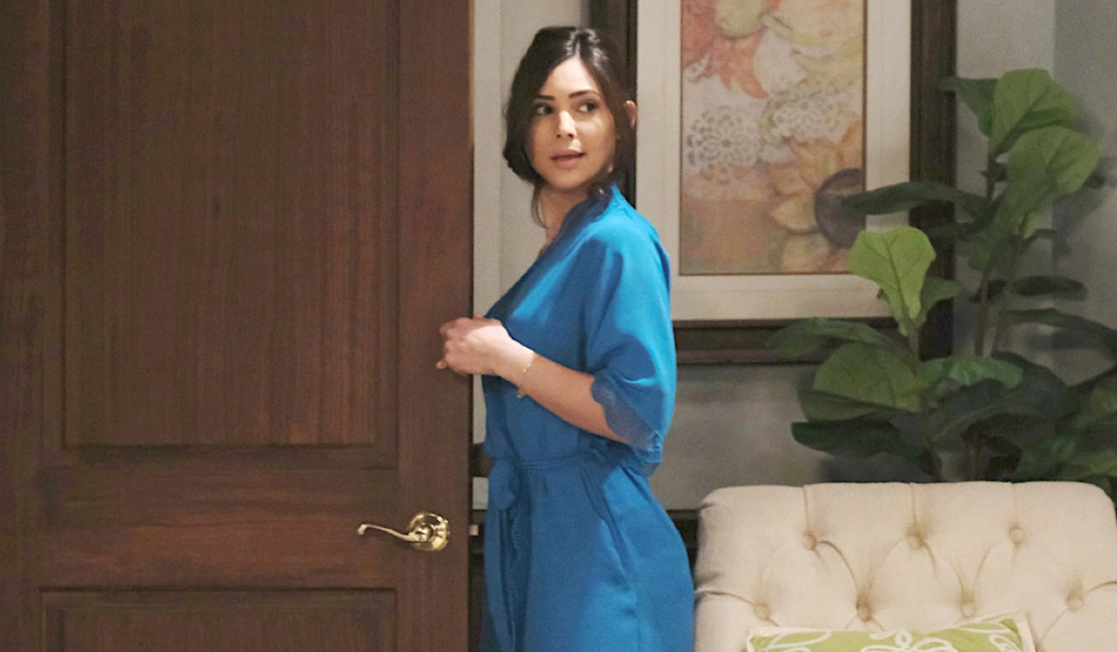 Dressed in a robe, Gabi glances back with a seductive look on Days of Our Lives