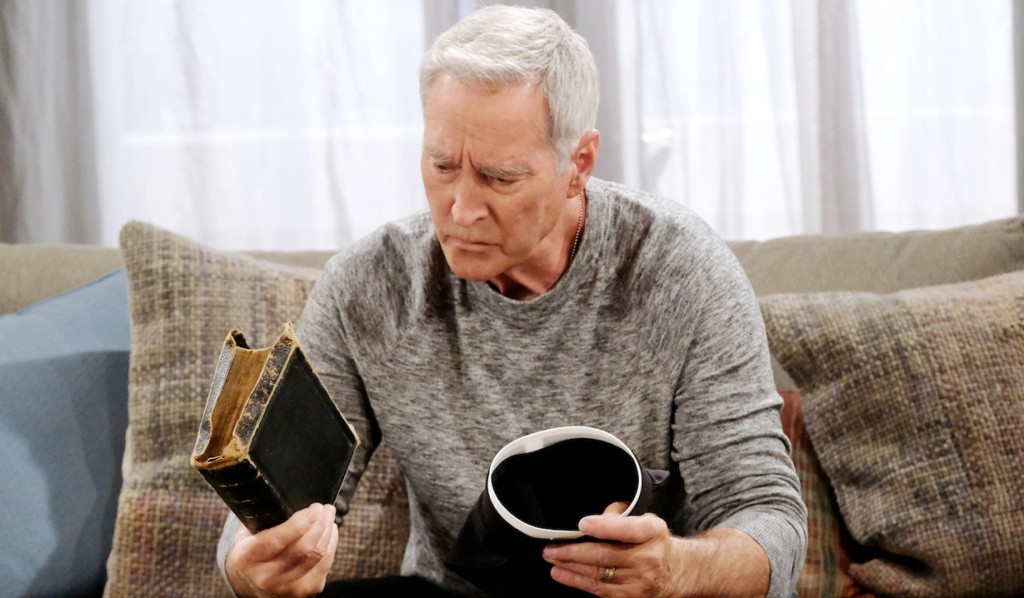 John holds a bible and a clerical collar while sitting on the couch on Days of Our Lives