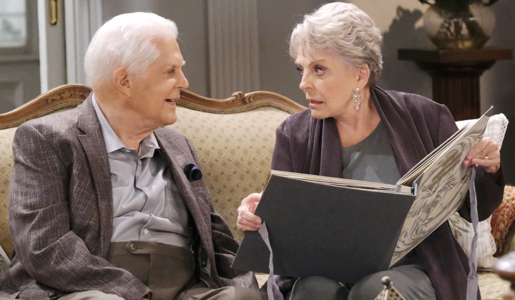 Julie and Doug look through a photo album on the couch at home on Days of Our Lives