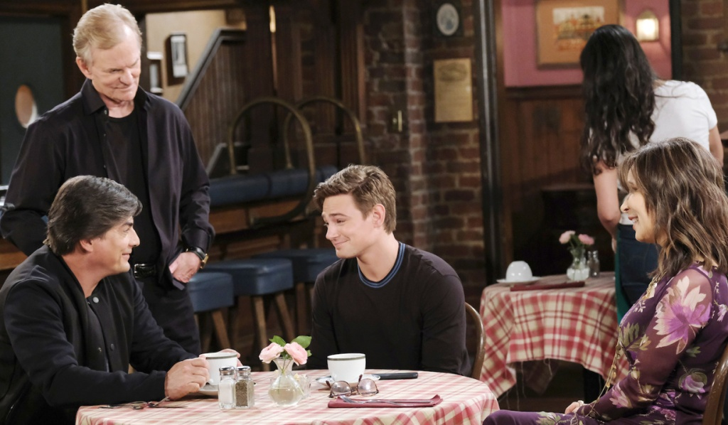 Lucas, Johnny and Kate sit smiling at a Brady's Pub table as Roman stands nearby looking at his grandson on Days of Our Lives