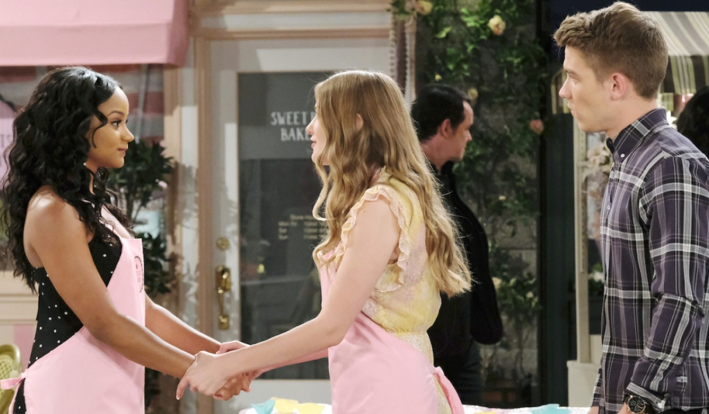 Tripp watches as Allie talks to Chanel while grasping her hands in front of Sweet Bits on Days of Our Lives