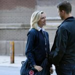 Brett and Casey stand out side smiling while standing close on Chicago Fire.