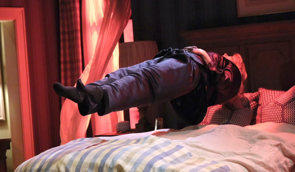 Marlena levitates over her bed as red light is cast on the room on Days of Our Lives