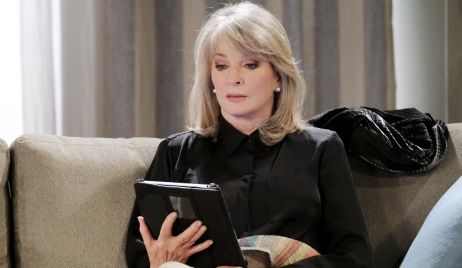 Marlena's eyes widen upon looking at her tablet on her couch on Days of Our Lives