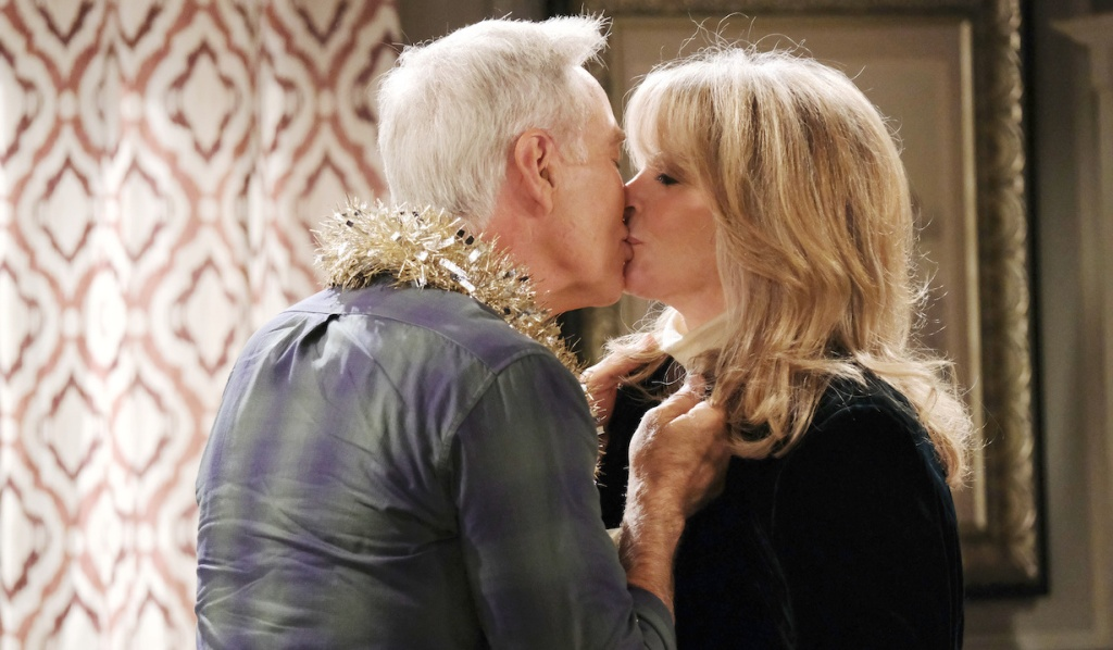 With garland wrapped around his neck, John kisses Marlena on Days of Our Lives
