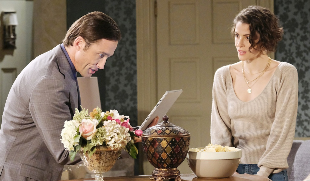 Sarah watches Philip look through his laptop on Days of Our Lives