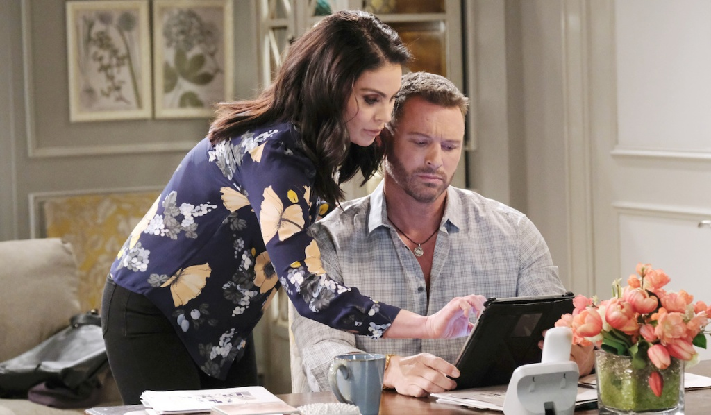 Chloe reads over Brady's shoulder on Days of Our Lives