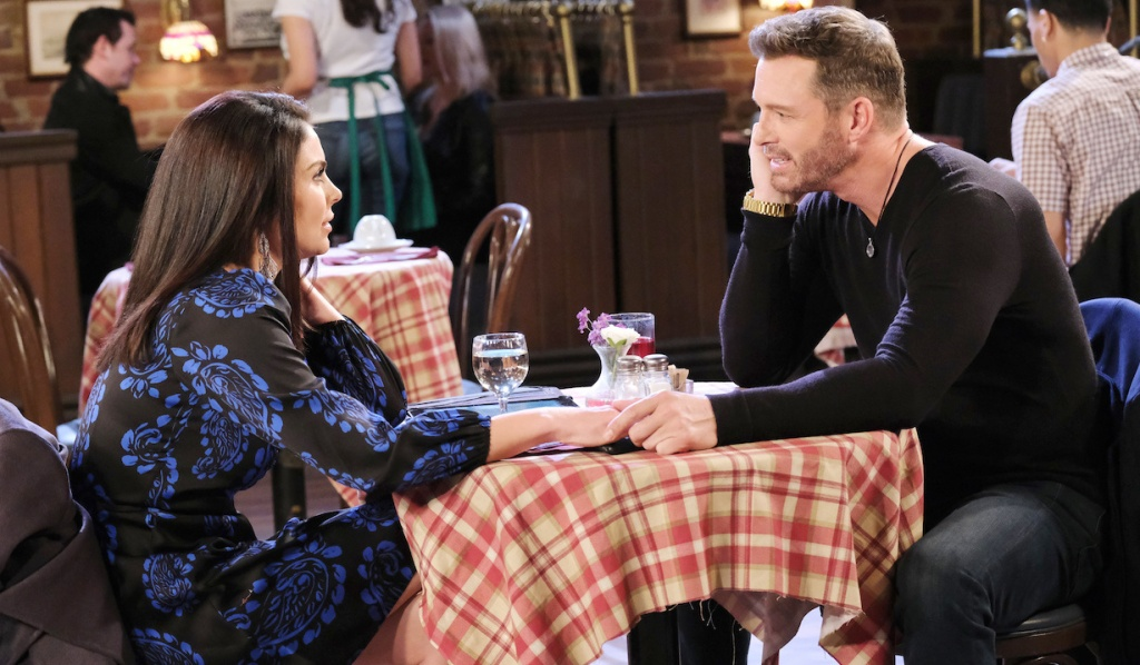 Chloe and Brady touch hands at Brady's Pub on Days of Our Lives