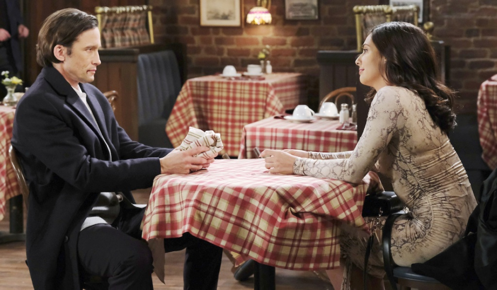 Blood on his face, Philip sits at a Brady's Pub table with Gabi on Days of Our Lives
