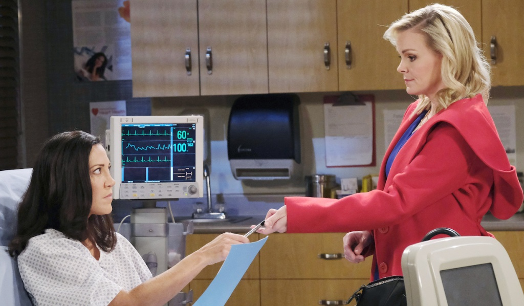 Belle hands Jan paperwork to sign on Days of Our Lives