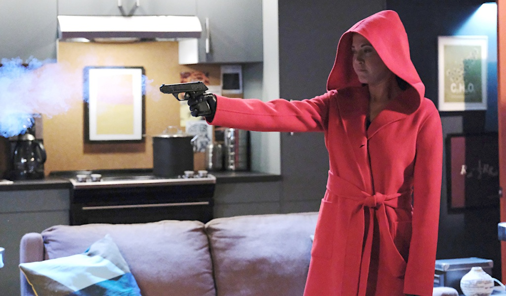 Jan in a red coat shoots a gun on Days of Our Lives