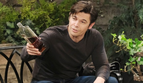 Xander extends a bottle of booze to someone in the park on Days of Our Lives