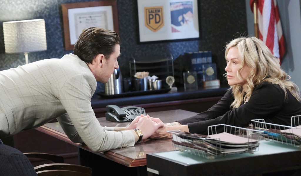 chad holds Kristen's hands across the table at the SPD on Days of Our Lives