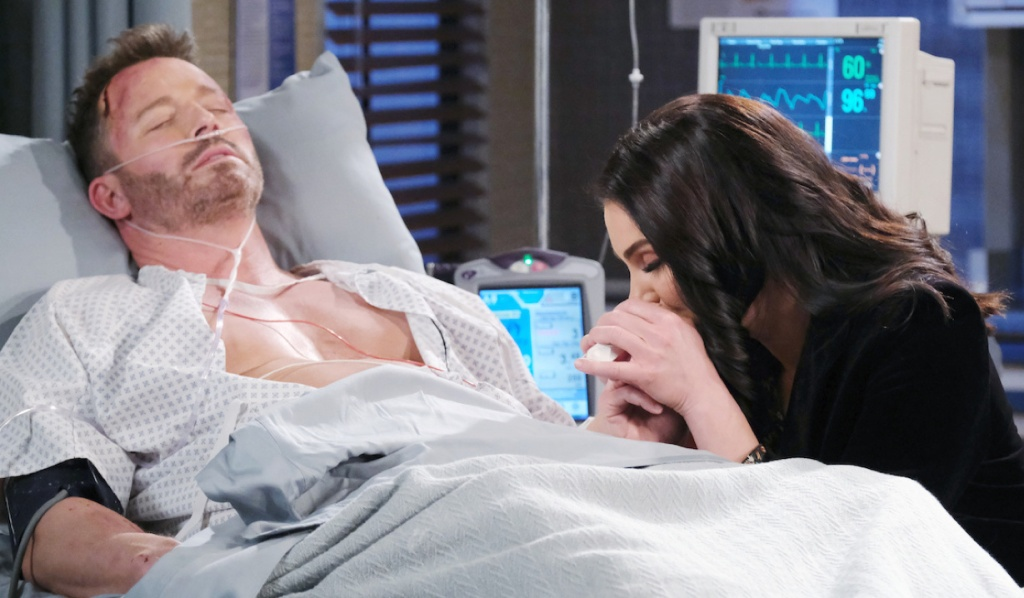 Chloe holds Brady's hand at his hospital bedside on Days of Our Lives
