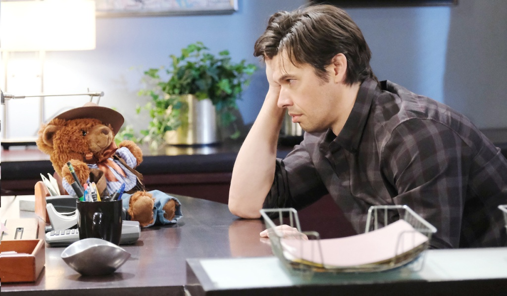 Xander drunkenly looks at a teddy bear at the Salem PD on Days of Our Lives