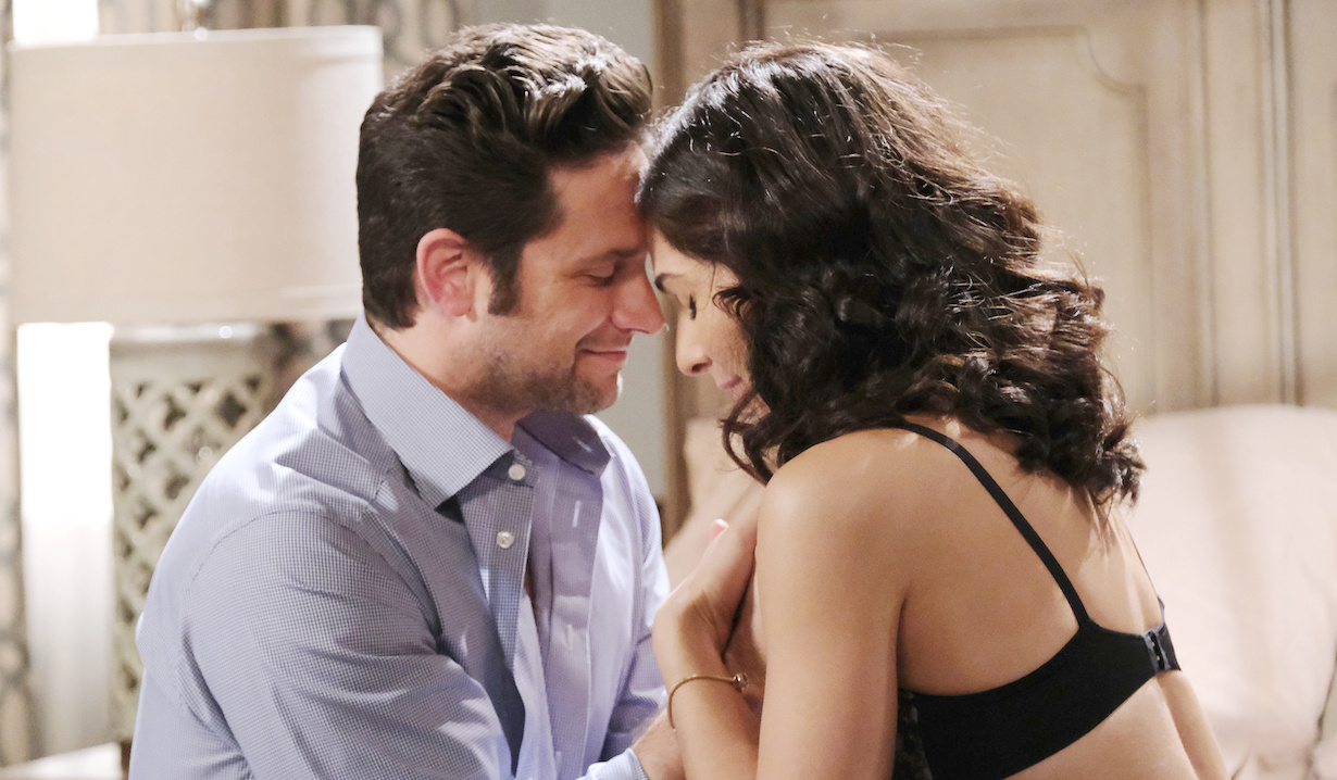 Jake and Gabi touch foreheads sitting on the bed on Days of Our Lives