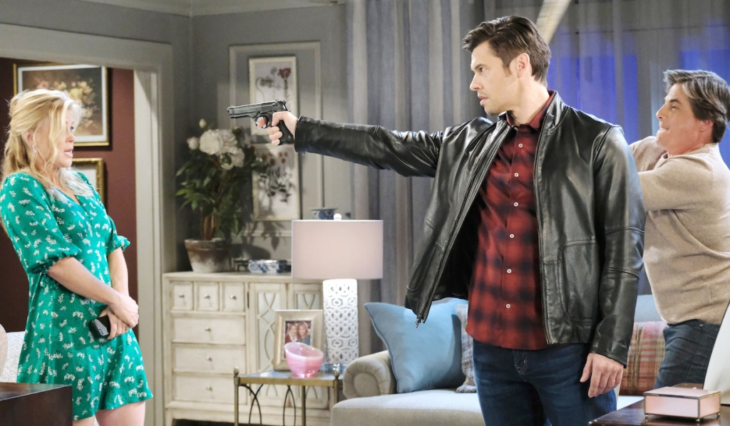 Lucas swings a bat at Xander who holds a gun on Sami on Days of Our Lives