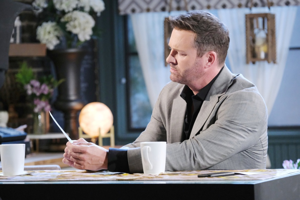Brady looks at a photo while sitting at the bar in Julie's Place on Days of Our Lives