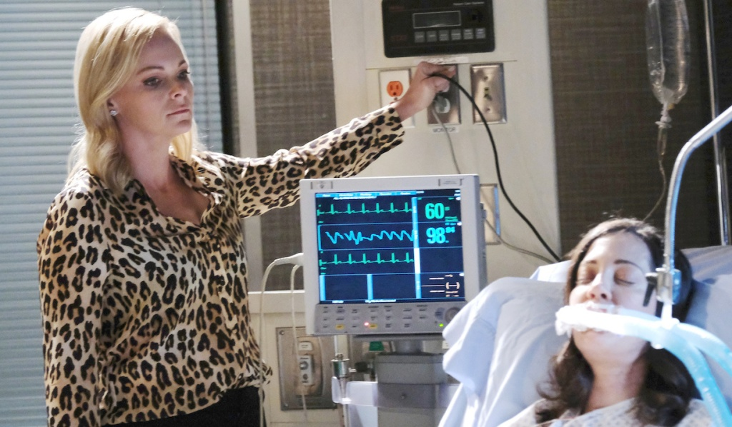 With her hand on the plug, Belle glares at Jan who is hooked up to machines on Days of Our Lives