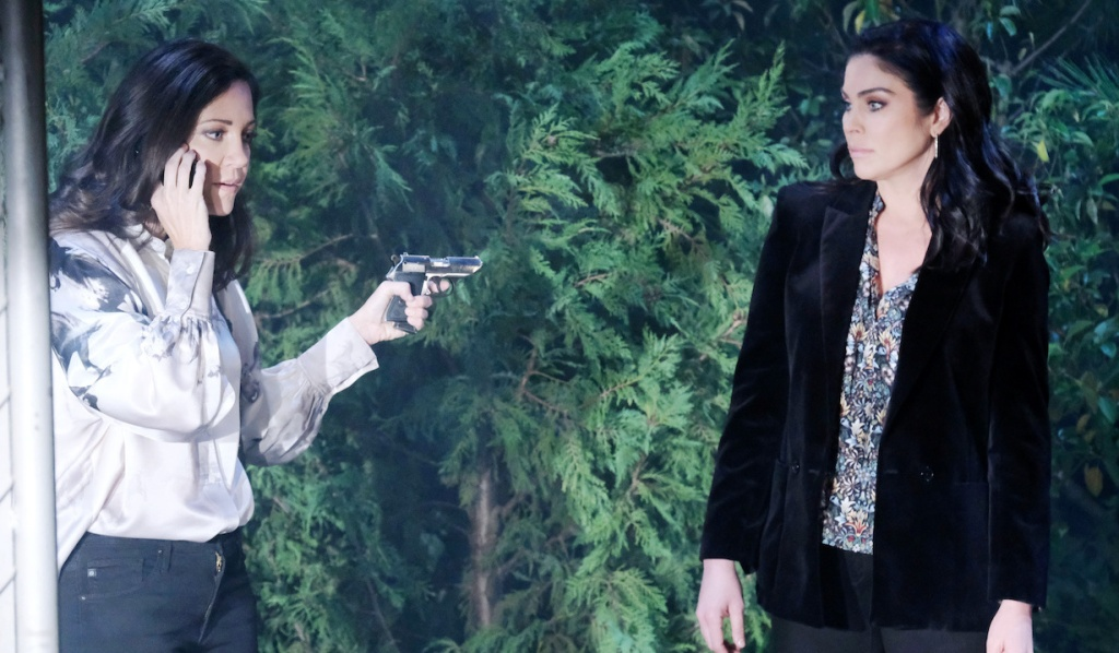 Jan holds a gun on Chloe while talking on a phone in the woods on Days of Our Lives