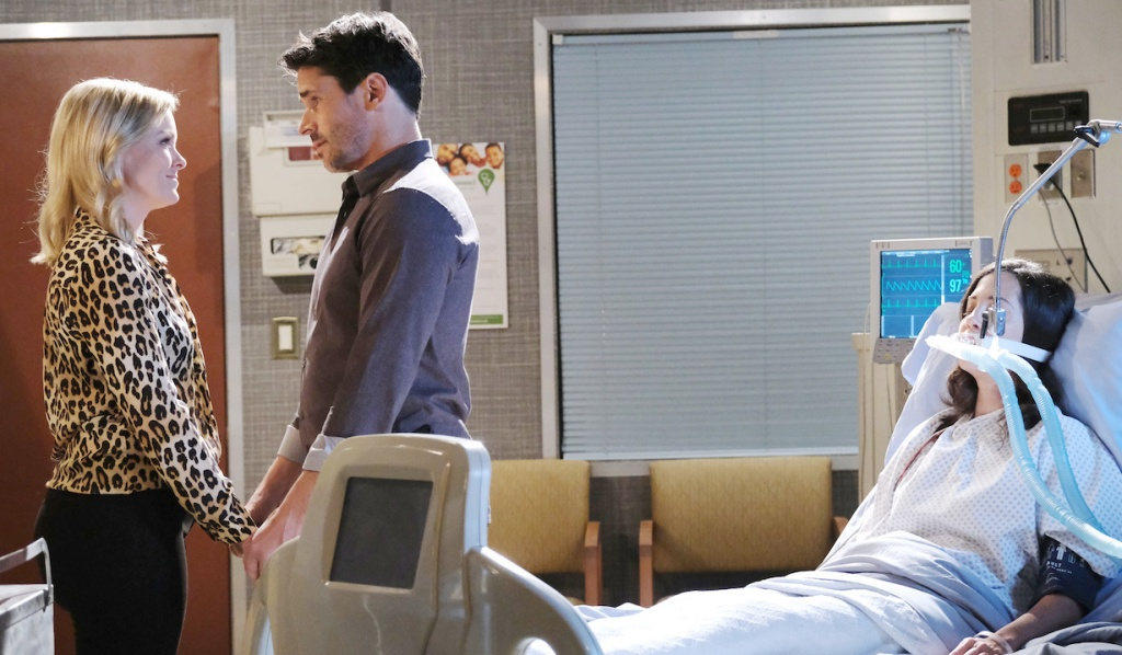 Jan and Shawn face each other while holding hands next to a comatose Jan's hospital bed on Days of Our Lives