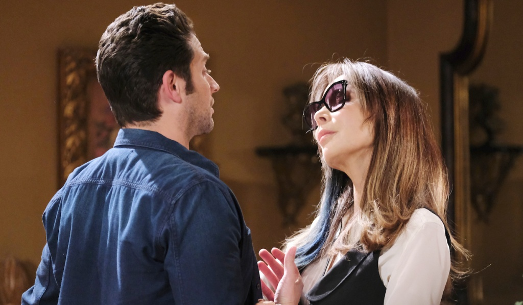 Wearing sunglasses, Kate looks up at Jake in their bedroom on Days of Our Lives