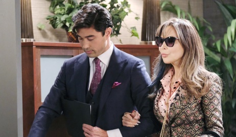 Wearing sunglasses, Kate links her arm in Li Shin's on Days of Our Lives