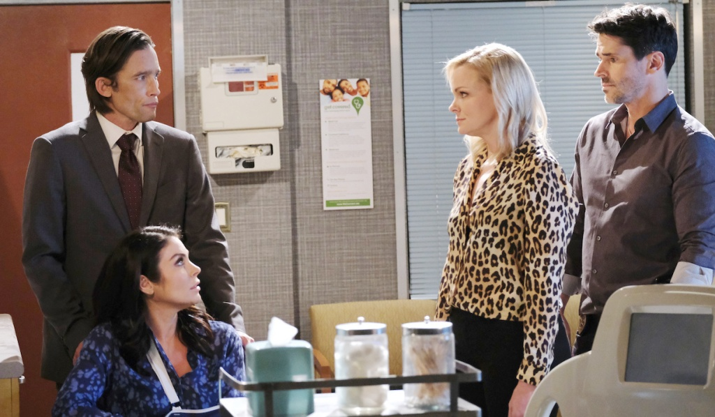 Philip stands behind Chloe, who sits in a wheelchair, while talking to Belle and Shawn on Days of Our Lives