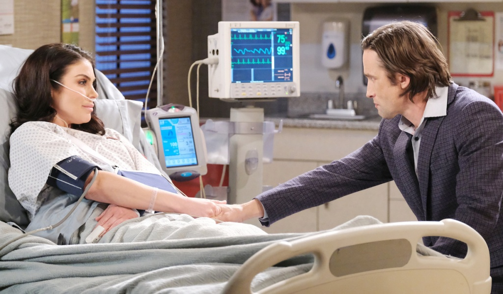 Philip holds Chloe's hand at her hospital bedside on Days of Our Lives