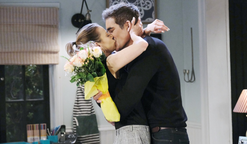 Rafe holds a bouquet of flowers as he kisses Ava in his kitchen on Days of Our Lives