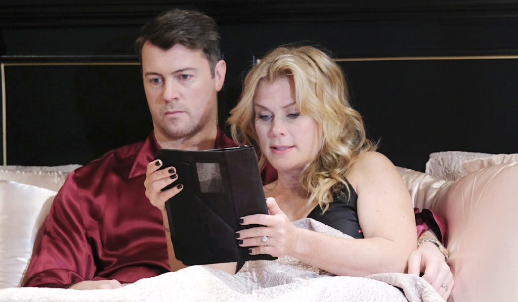 EJ sits expressionless in bed as Sami reads from a tablet on Days of Our Lives