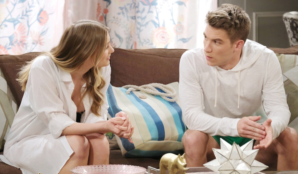 Tripp and Allie in beachwear talking on the couch on Days of Our Lives