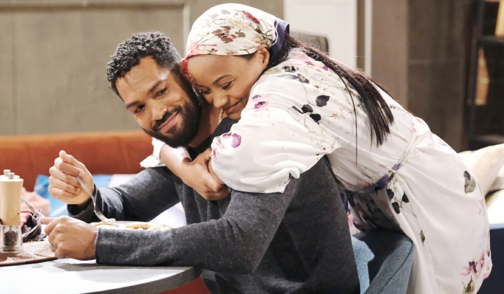 Chanel hugs Eli from behind at the kitchen table on Days of Our Lives