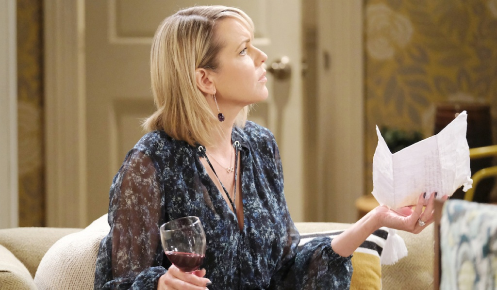 Nicole holds a letter in one hand and a glass of wine in another on Days of Our Lives