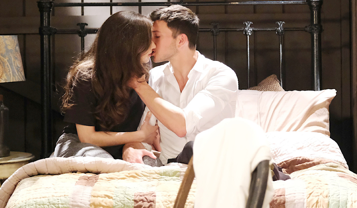 Ben and Ciara kiss while sitting on a bed at the cabin on Days of Our Lives