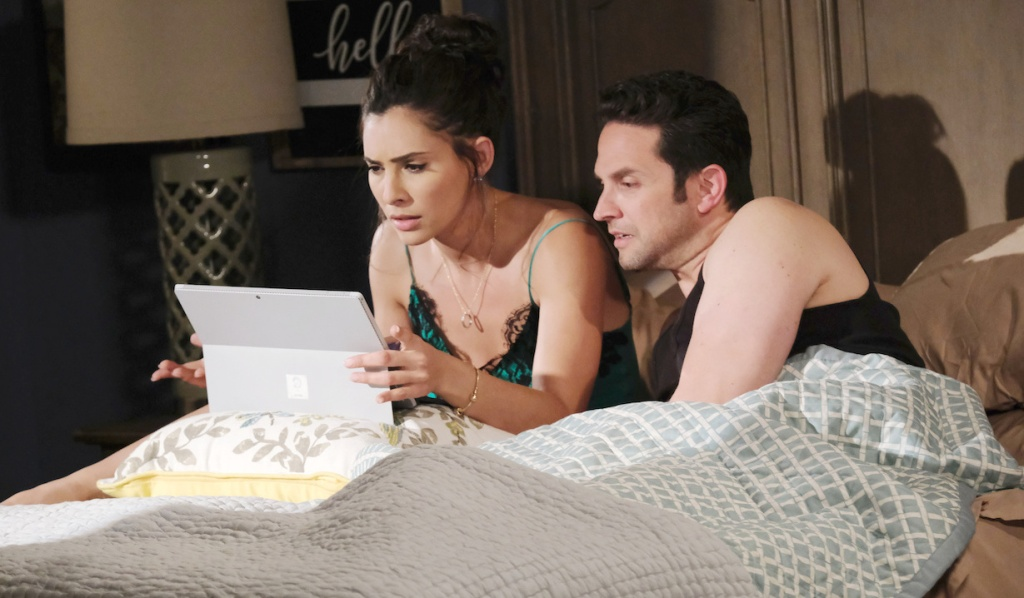 Gabi and Jake pour over her laptop in bed on Days of Our Lives