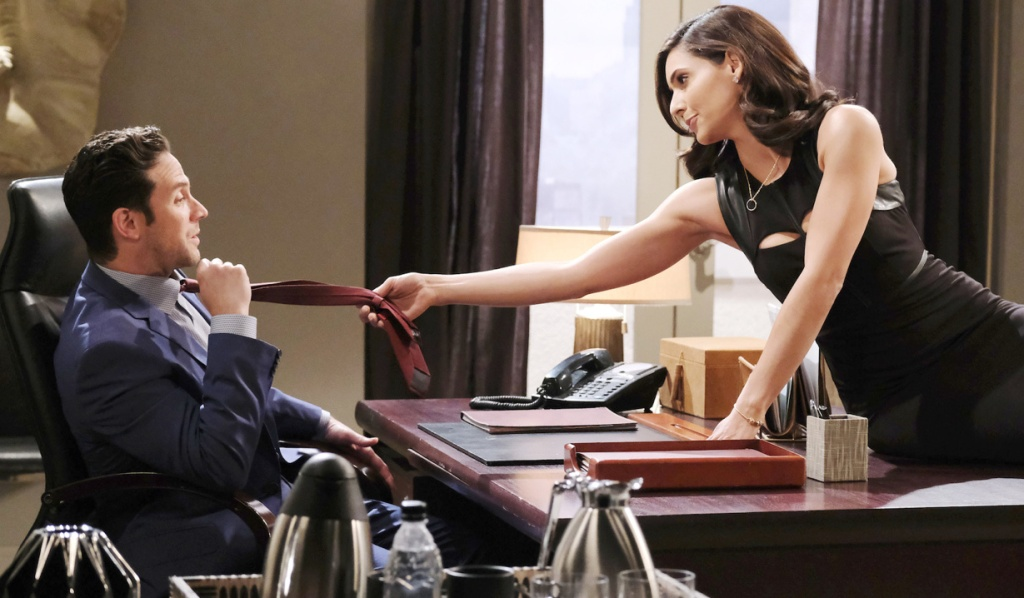 Gabi grabs Jakes tie from across the desk at Titan on Days of Our Lives