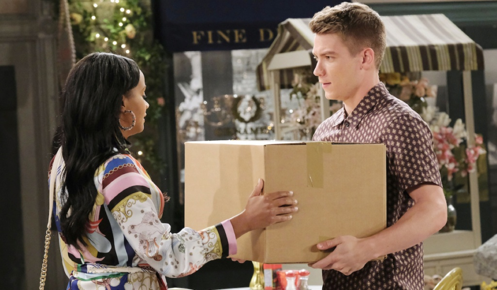 Tripp carries a box for Chanel in the Square on Days of Our Lives