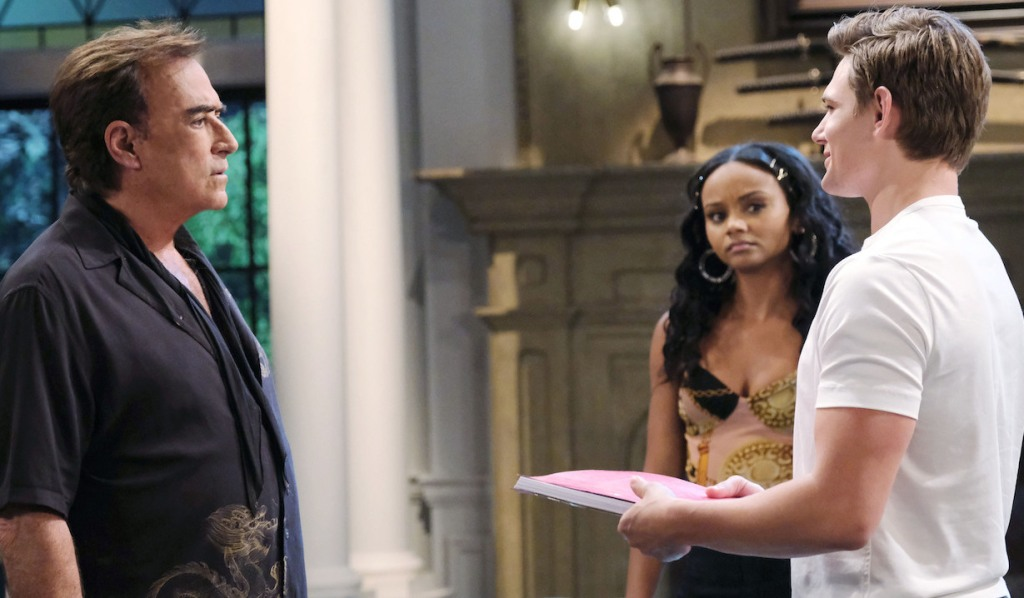 Chanel watches as Johnny holds out Will's script to Tony in the DiMera living room on Days of Our Lives