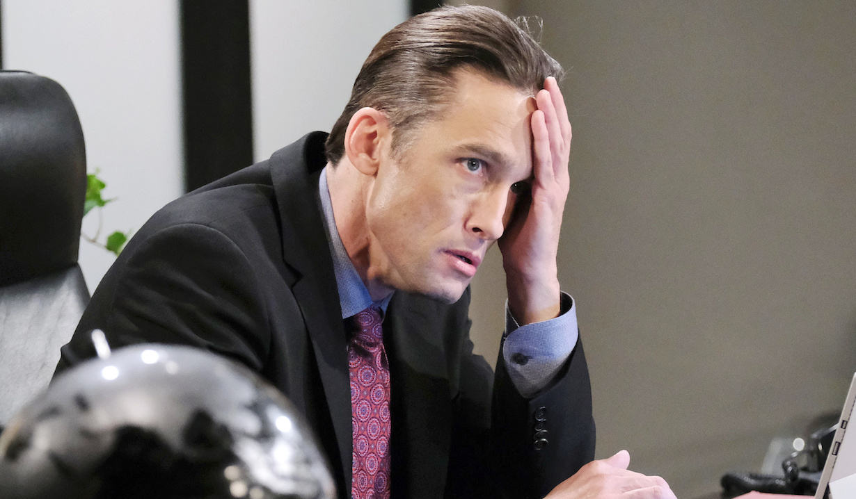 Enraged, Philip holds his head in his hand as he sits at his desk on Days of Our Lives