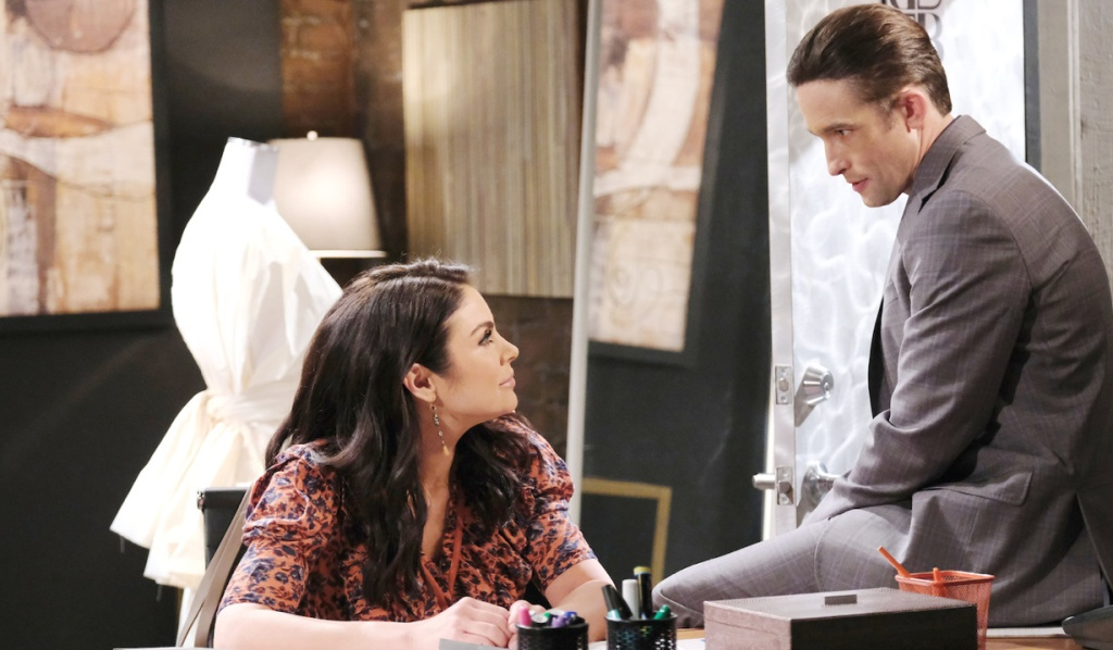 Philip sits on a corner of a desk while talking to Chloe on Days of Our Lives