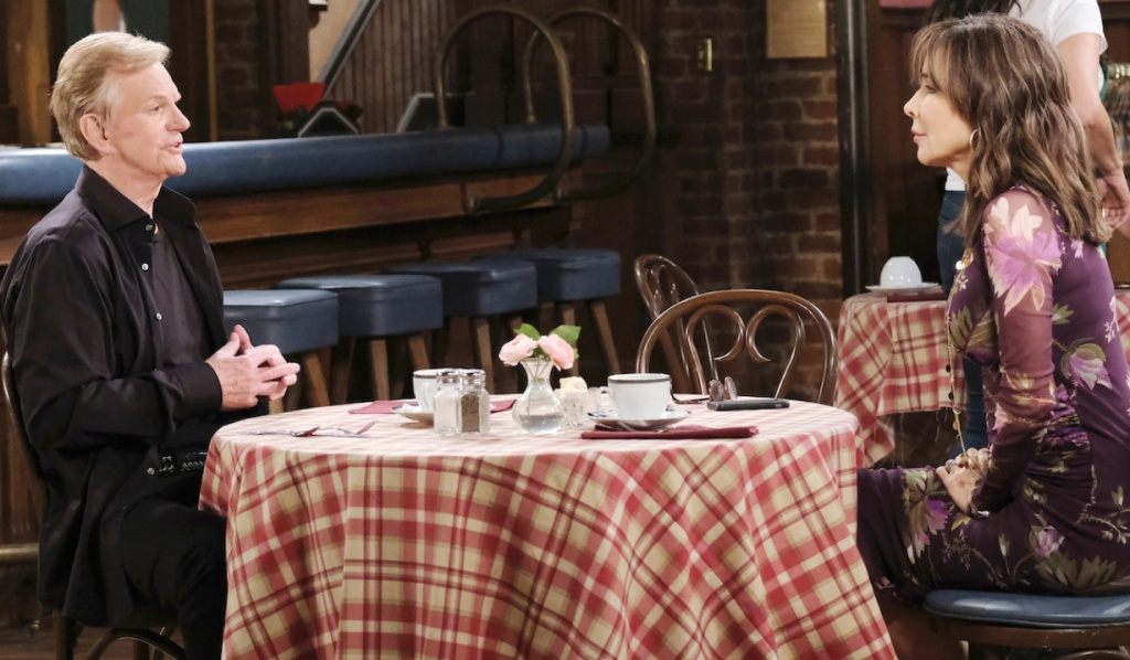 Roman and Kate sit across a table from each other in Brady's Pub on Days of Our Lives