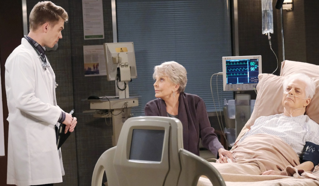 Tripp talks with Julie who is sitting by Doug's bedside in the hospital on Days of Our Lives