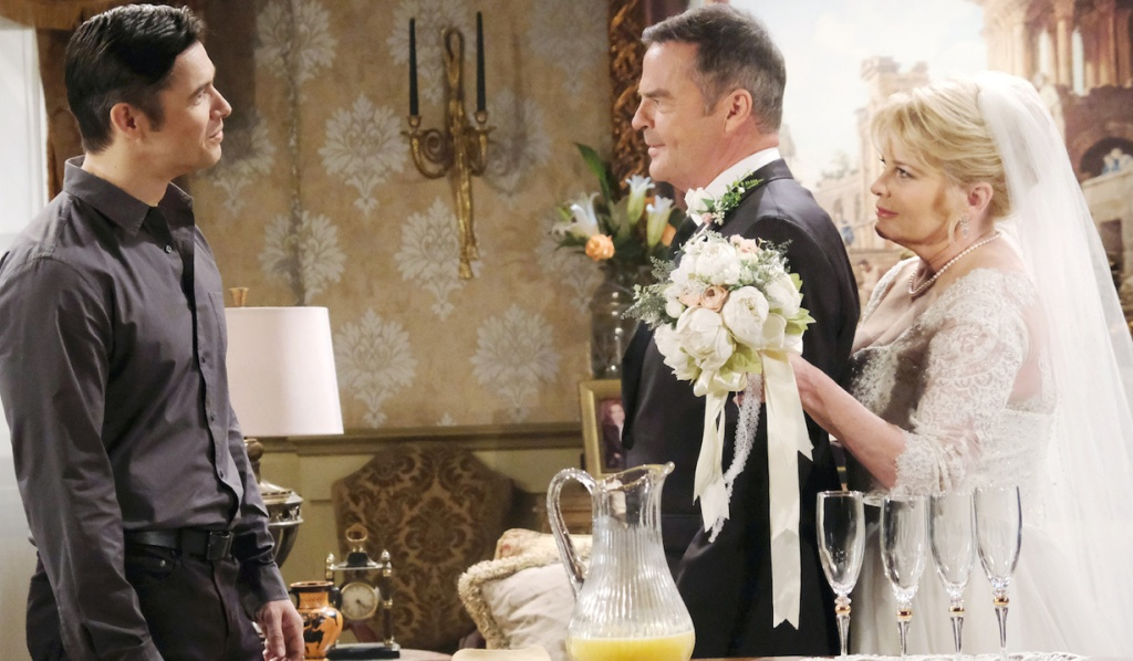 Bonnie, in her wedding dress, stands behind Justin as he confronts Xander on Days of Our Lives