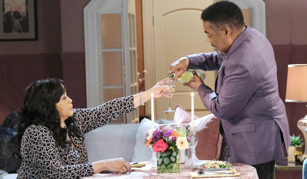 Abe pours Paulina a glass of wine as she sits at a candle lit table in her apartment on Days of Our Lives