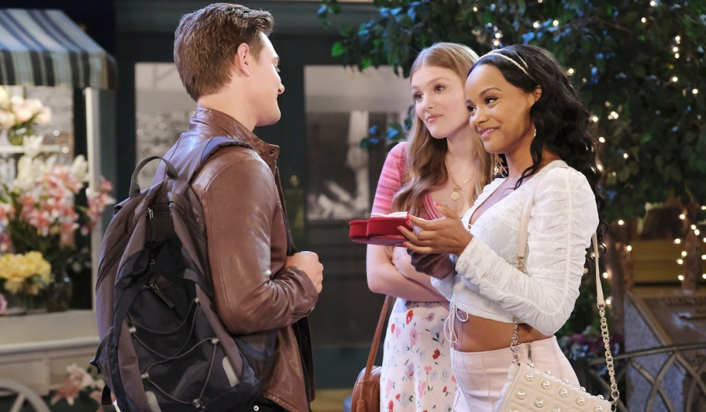 Allie gives a disdainful look as Johnny hands a smiling Chanel a gift in the Square on Days of Our Lives