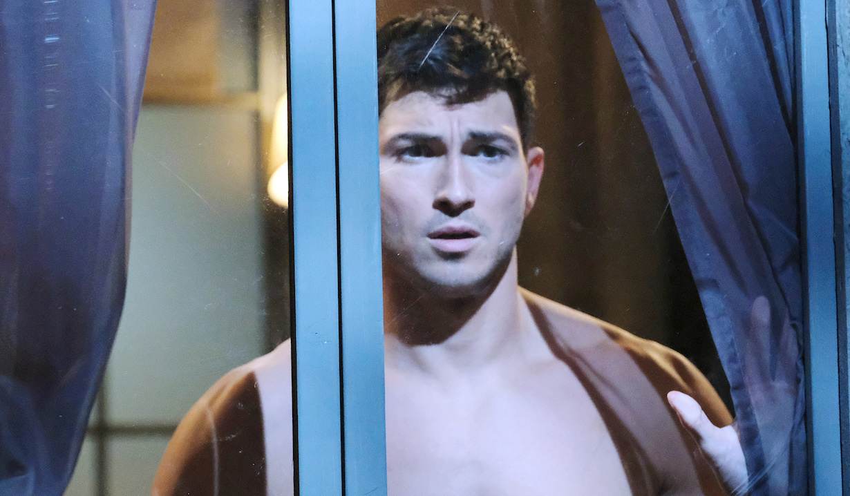 A shirtless and distraught looking Ben stares out his window on Days of Our Lives