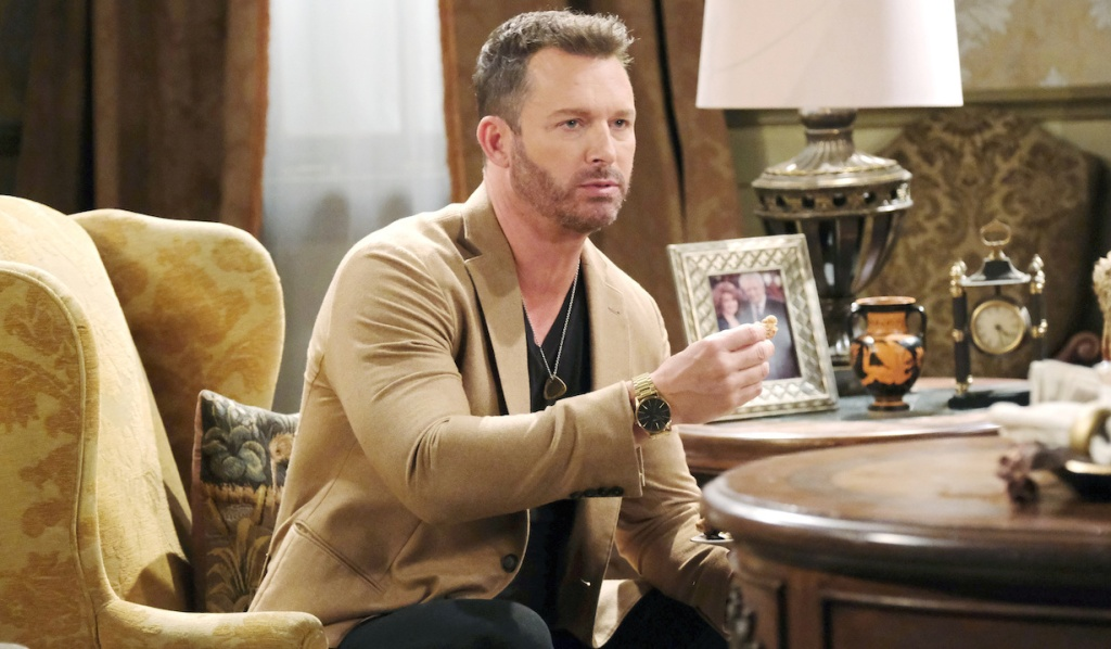 Brady eats a muffin while sitting in an armchair in the Kiriakis mansion on Days of Our Lives